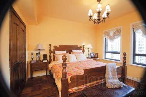 卧室中的木床遵从欧洲风格,床前的脚榻是与餐桌呼应的扑克图案.