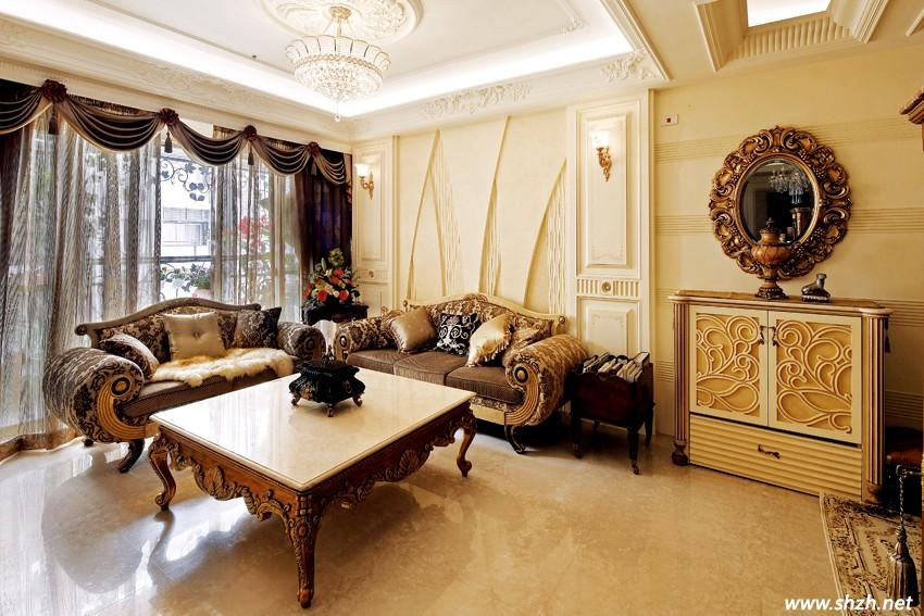 沙发背墙的精工处理则是另一重赏心悦目的风景,同样以清爽优雅的象牙米白色系为基底,中央透过多层次浮雕的技巧,展现现代抽象画一般的立体视觉效果, 两侧对称的线条分割造型,点缀精致鎏金壁灯,搭配量身订制的宫廷风味家具,同时也能呼应客厅上方细腻的艺术天花造型与置中的辉煌水晶灯饰,在光影缤纷交织 的情境中,巧妙提升室内高度并强化空间的大器指数。    由客厅准备前往餐厅的动线沿途左侧,设计师发挥独到的构图巧思,精选一座古典精品柜与成双的优雅单椅,打造出一处饶富情趣的过渡端景,后方背景墙以柔 和的波纹立面处理,烘